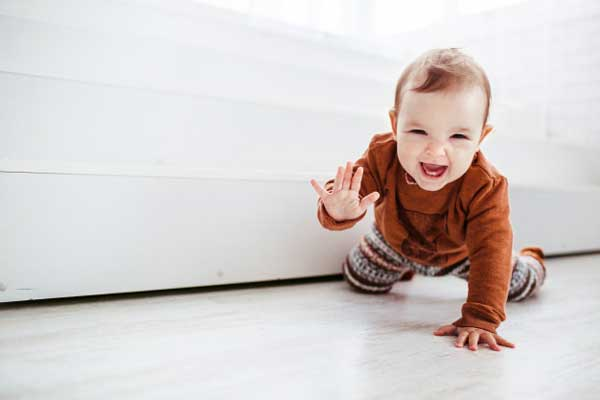 szczesliwy dziecko w pomaranczowym pulowerze bawic sie z piorkiem na podloga 8353 185